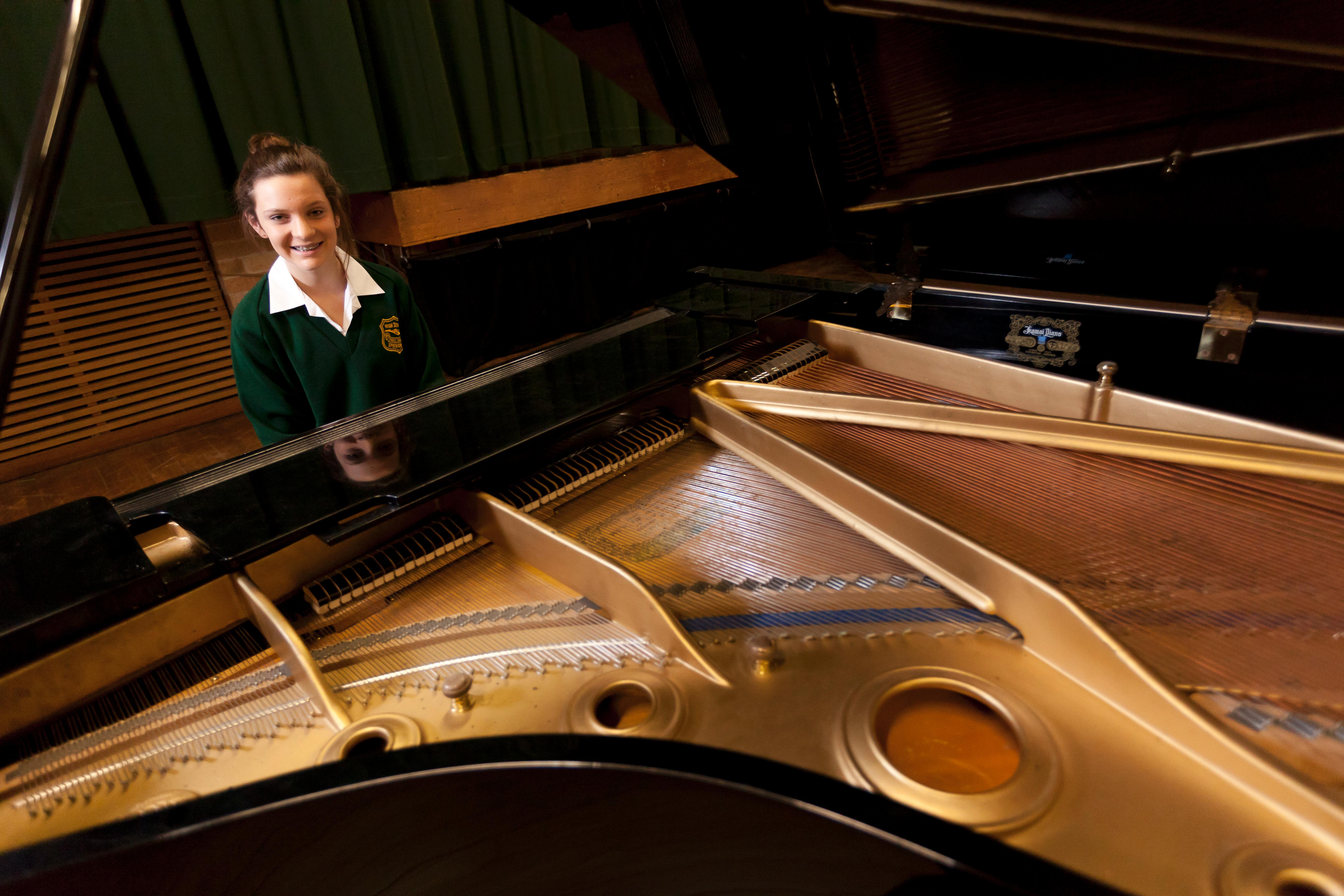 Student playing grand piano